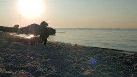 Αθλητικό κορίτσι σε ένα μαύρο κομπινεζόν και δερματοστιξία στο ισχίο της που κάνει τη γιόγκα στην άμμο κοντά στη θάλασσα ή τον ωκ απόθεμα βίντεο