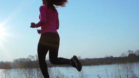Αθλητικό κοριτσιών κατά μήκος της όχθης ποταμού κατά τη διάρκεια της ανατολής ή του ηλιοβασιλέματος η υγιής έννοια τρόπου ζωής τη απόθεμα βίντεο