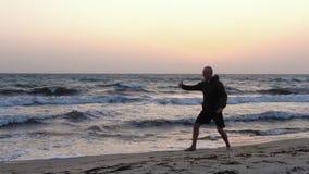Αθλητικό wushu άσκησης ατόμων στην ακτή στην ανατολή απόθεμα βίντεο