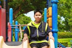 Αθλητισμός και έννοια τρόπου ζωής: Νέα ασιατική συνεδρίαση αγοριών στην παιδική χαρά στην υπαίθρια παιδική χαρά Στοκ Εικόνα
