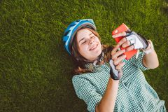 Αθλητισμός και τεχνολογία θέματος Ο όμορφος καυκάσιος σπουδαστής γυναικών με το οδοντωτό χαμόγελο βρίσκεται πίσω πράσινη χλόη υπο στοκ φωτογραφία με δικαίωμα ελεύθερης χρήσης