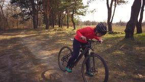 Αθλητισμός και τουρισμός θέματος στη φύση Καυκάσιος νέος ποδηλάτης γυναικών σε ένα κράνος και sportswear που οδηγούν ένα ποδήλατο φιλμ μικρού μήκους
