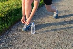 Αθλητισμός και τρέχοντας έννοια ιδέας δένοντας κορδόνια δρομέων νεαρών άνδρων Στοκ Εικόνα