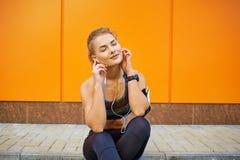 Αθλητισμός κοριτσιών που ακούει τη μουσική με τα ακουστικά που κάθονται στο πορτοκάλι Στοκ Εικόνες