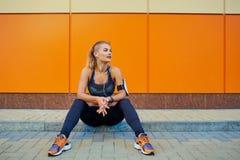 Αθλητισμός κοριτσιών που ακούει τη μουσική με τα ακουστικά που κάθονται στο πορτοκάλι Στοκ Φωτογραφία