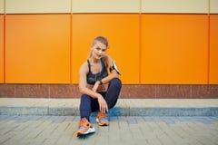 Αθλητισμός κοριτσιών που ακούει τη μουσική με τα ακουστικά που κάθονται στο πορτοκάλι Στοκ φωτογραφία με δικαίωμα ελεύθερης χρήσης