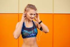Αθλητισμός κοριτσιών που ακούει τη μουσική με τα ακουστικά που κάθονται στο πορτοκάλι Στοκ εικόνα με δικαίωμα ελεύθερης χρήσης
