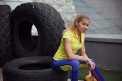 Αθλητισμός, μετά από να εκπαιδεύσει με το ελαστικό αυτοκινήτου Συνεδρίαση φιλάθλων χαμόγελου νέα θηλυκή σε μια ρόδα Στοκ Εικόνα