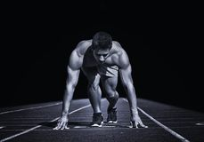 αθλητισμός Νέος δρομέας στη γραμμή έναρξης Απομονωμένος στο Μαύρο Στοκ Εικόνες