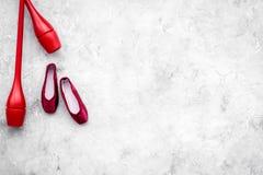 Αθλητισμός ομορφιάς για την έννοια κοριτσιών Το Maces για τα ρυθμικά παπούτσια γυμναστικής και μπαλέτου στην γκρίζα τοπ άποψη υπο Στοκ Εικόνες