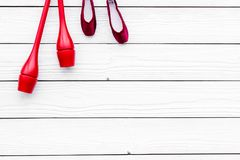 Αθλητισμός ομορφιάς για την έννοια κοριτσιών Το Maces για τα ρυθμικά παπούτσια γυμναστικής και μπαλέτου στην άσπρη ξύλινη τοπ άπο Στοκ Φωτογραφία