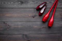 Αθλητισμός ομορφιάς για την έννοια κοριτσιών Το Maces για τα ρυθμικά παπούτσια γυμναστικής και μπαλέτου στη σκοτεινή ξύλινη τοπ ά Στοκ Εικόνα