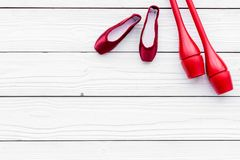 Αθλητισμός ομορφιάς για την έννοια κοριτσιών Το Maces για τα ρυθμικά παπούτσια γυμναστικής και μπαλέτου στην άσπρη ξύλινη τοπ άπο Στοκ Εικόνες