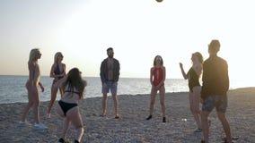 Αθλητισμός παραλιών, επιχείρηση των φίλων που παίζουν με τη σφαίρα στην πετοσφαίριση στον ωκεανό ακτών απόθεμα βίντεο