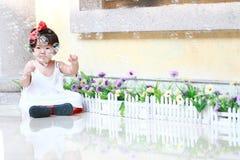 Αθώες κινεζικές φυσαλίδες παιχνιδιού κοριτσάκι σε έναν κήπο Στοκ Φωτογραφίες