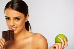 Αθλήτρια που κάνει την επιλογή μεταξύ του υγιούς μήλου Στοκ φωτογραφίες με δικαίωμα ελεύθερης χρήσης