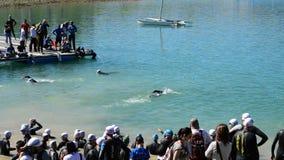 Αθλητές που κολυμπούν σε μια λίμνη πριν από την έναρξη ένα triatlhon φιλμ μικρού μήκους
