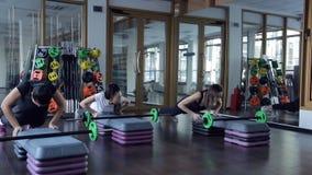 Αθλητές ώθηση-UPS στον προσομοιωτή στη γυμναστική που επιλύουν στο στούντιο ικανότητας απόθεμα βίντεο