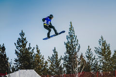 Αθλητής άλματος και πτήσης snowboarder σε ένα υπόβαθρο του μπλε ουρανού Στοκ Εικόνα