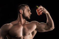 Αθλητής γυμνοστήθων που κρατά το κόκκινο πιπέρι κουδουνιών Στοκ φωτογραφία με δικαίωμα ελεύθερης χρήσης