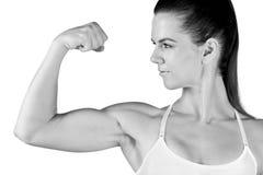 Αθλητής γυναικών που παρουσιάζει δικέφαλους μυς Στοκ φωτογραφίες με δικαίωμα ελεύθερης χρήσης