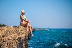 Αθλητής γυναικών σε έναν βράχο θαλασσίως Στοκ Εικόνες