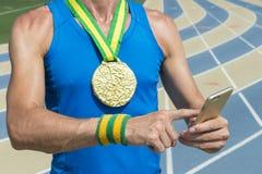 Αθλητής διαδρομής χρυσών μεταλλίων που χρησιμοποιεί το κινητό τηλέφωνο Στοκ Φωτογραφίες