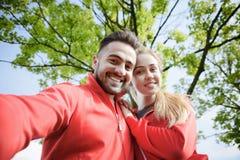 Αθλητής και γυναίκα που κάνουν selfies στο πάρκο στοκ εικόνες