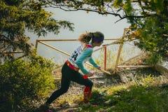 Αθλητής κοριτσιών που τρέχει μέσω του δάσους, στα χέρια της ένα μπουκάλι νερό isotonic στοκ φωτογραφία