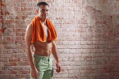 Αθλητής μετά από ένα workout με την πετσέτα στο παλαιό κόκκινο υπόβαθρο τούβλων Στοκ Εικόνες