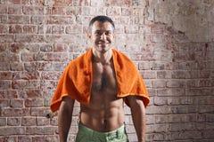 Αθλητής μετά από ένα workout με την πετσέτα στο παλαιό κόκκινο υπόβαθρο τούβλων Στοκ φωτογραφία με δικαίωμα ελεύθερης χρήσης