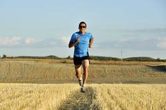 Αθλητής με τα γυαλιά ηλίου που τρέχουν υπαίθρια στο έδαφος τομέων αχύρου στη μετωπική προοπτική Στοκ φωτογραφία με δικαίωμα ελεύθερης χρήσης