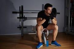 αθλητής που κουράζεται λυπημένος για να ενεργήσει συλλογισμένα καθμένος στη γυμναστική στοκ φωτογραφία