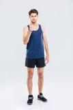 0 αθλητής που παρουσιάζει πυγμή πέρα από το γκρίζο υπόβαθρο Στοκ Εικόνες
