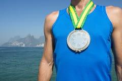 Αθλητής χρυσών μεταλλίων που στέκεται την παραλία Ρίο Ipanema Στοκ Φωτογραφία