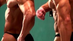 Αθλητικά αρσενικά bodybuilders που θέτουν το αθλητικό γεγονός ανταγωνισμών απόθεμα βίντεο