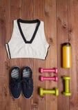 Αθλητικά εξαρτήματα: ενδύματα, παπούτσια, βάρη, μπουκάλι στο ξύλινο υπόβαθρο Στοκ φωτογραφία με δικαίωμα ελεύθερης χρήσης
