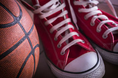Αθλητικά πάνινα παπούτσια και σφαίρα καλαθιών Στοκ Φωτογραφία