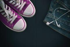 Αθλητικά παπούτσια και ένα τεμάχιο των τζιν σε ένα μαύρο ξύλινο backgroun Στοκ φωτογραφία με δικαίωμα ελεύθερης χρήσης