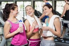 Αθλητικές χαμογελώντας γυναίκες που θέτουν με το μπουκάλι νερό Στοκ Εικόνες