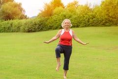 Αθλητική ανώτερη γυναίκα που εκτελεί τις ασκήσεις ισορροπίας Στοκ Εικόνες