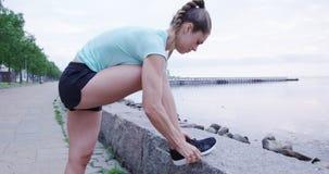 Αθλητική γυναίκα που δένει τις δαντέλλες της πρίν τρέχει στοκ εικόνα