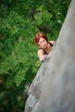 Αθλητική γυναίκα που αναρριχείται στον απότομο τοίχο απότομων βράχων στο θερινό χρόνο Στοκ Εικόνες