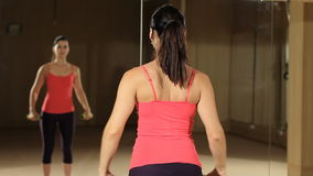 Αθλητική γυναίκα που αντλεί επάνω τους μυς με τους αλτήρες Πρότυπο ικανότητας που κοιτάζει στον καθρέφτη απόθεμα βίντεο