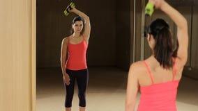 Αθλητική γυναίκα που αντλεί επάνω τους μυς με τους αλτήρες Πρότυπο ικανότητας που κοιτάζει στον καθρέφτη φιλμ μικρού μήκους
