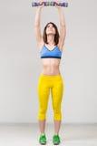 Αθλητική γυναίκα που αντλεί επάνω τους μυς με τους αλτήρες στοκ εικόνες με δικαίωμα ελεύθερης χρήσης