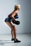 Αθλητική γυναίκα που αντλεί επάνω muscules με τους αλτήρες στοκ φωτογραφίες