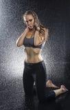 Αθλητική γυναίκα που γονατίζει στο στούντιο με τον ψεκασμό νερού στοκ φωτογραφίες