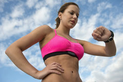 Αθλητική γυναίκα που χρησιμοποιεί το όργανο ελέγχου ποσοστού καρδιών στοκ εικόνες