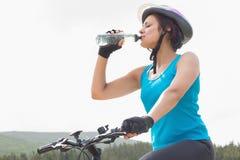 Αθλητική γυναίκα στο πόσιμο νερό ποδηλάτων βουνών Στοκ Εικόνα